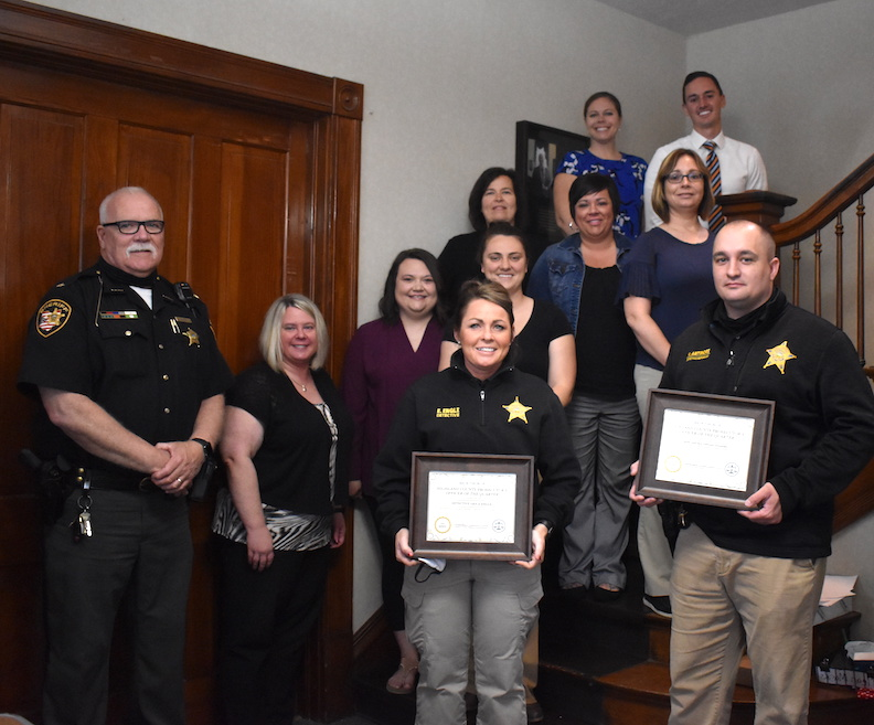 Highland County Sheriff's Detectives Erica Engle and Vincent Antinore are pictured with their Highland County Prosecutor's Officer of the Quarter Awards, as HCPO staff and Sheriff Donnie Barrera look on. Pictured are: (front, l-r) Sheriff Donnie Barrera, office administrator Kathryn Allen and Detectives Erica Engle and Vincent Antinore; (second row, l-r) victim advocates Shelby Burchett and Kayla Conrad; (third row, l-r) office assistant Karen Bridges, administrative assistant Tara Decker and prosecutor Anneka Collins; and (back row, l-r) assistant prosecutors Molly Bolek and Adam King. (HCP Photo/Caitlin Forsha)